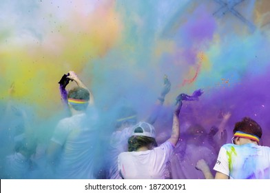 "KALAMAZOO, MICHIGAN, USA - April 12, 2014: Participants celebrate the arrival of spring and the end of a 5K ""fun run"" by creating a multicolored fog of colored powder around themselves."