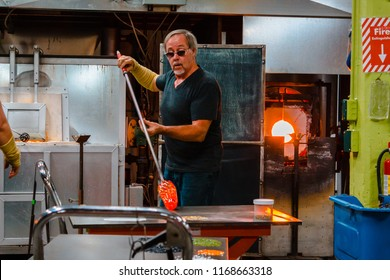 Kalamazoo, Michigan / USA - December 4th 2015: Adding colored glass to molten glass to give it some color