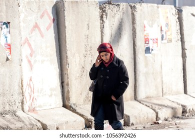 Kalandia, Palestine, January 12, 2011: A woman is passing a concrete wall near Kalandia check point built by Israel to stop Palestinians commuting in East Jerusalem.