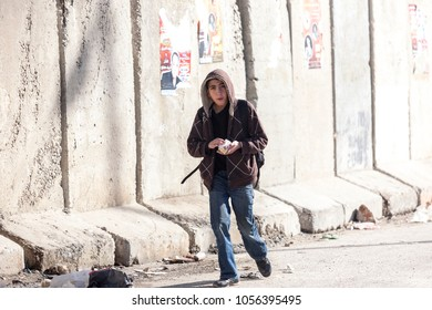 Kalandia, Palestine, January 12, 2011: A boy is passing a concrete wall near Kalandia check point built by Israel to stop Palestinians commuting in East Jerusalem.