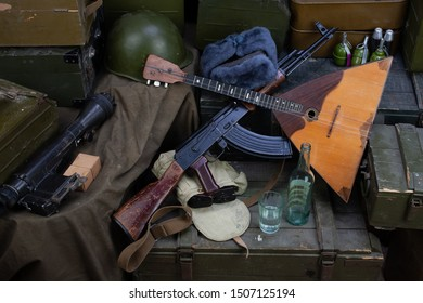 Kalashnikov AK 47 with ammunitions, vodka and balalaika on army green box background