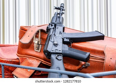 Kalashnikov ak-47 and vintage leather travel suitcases