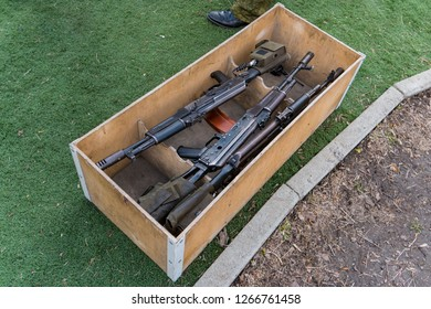 Kalashnikov assault rifles in a wooden box. Arms trade. illegal sale of weapons. An automatic weapon with a sniper scope in wood box