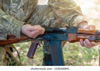 Kalashnikov automatic machine gun closeup in the hands of the military. Male hands charge a Kalashnikov assault rifle. Avtomatic rifle closeup