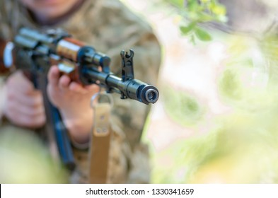 Kalashnikov automatic machine gun closeup in the hands of the soldier. Male hands hold a Kalashnikov assault rifle. Avtomatic rifle closeup. Concept military soldier pointed rifle on you.