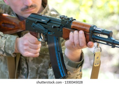 Kalashnikov automatic machine gun closeup in the hands of the military. Male hands hold a Kalashnikov assault rifle. Avtomatic rifle closeup