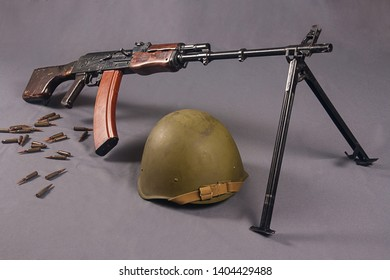 Kalashnikov light machine gun with a Soviet helmet