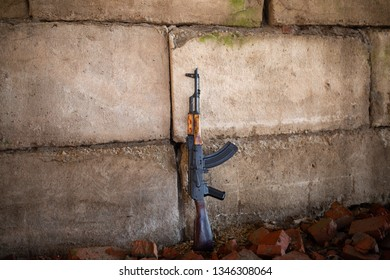 a Kalashnikov rifle on the brick background of the war