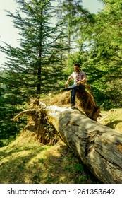 Kalatop Wildlife Sanctuary, Himachal Pradesh, India; 12-March-2018; sitting on a fallen tree, posing, self portrait, Kalatop Wildlife Sanctuary