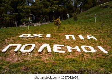 """Kalavryta Greece March 18 2016- memorial site where Greeks were massacred by germans during second world war in 1943 """"No more wars"""" is the phrase written  in greek which dominates on the grass."""