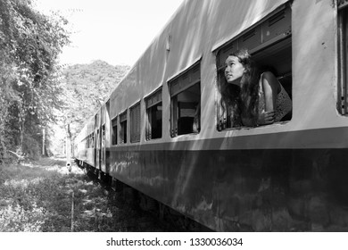 KALAW, MYANMAR - 23 NOVEMBER, 2018: Black and white picture of beautiful young woman posing at trains window in Kalaw, Myanmar