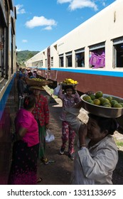 KALAW, MYANMAR - 23 NOVEMBER, 2018: Vertical picture of traditional burmese women selling fruits on the railway in Kalaw, Myanmar