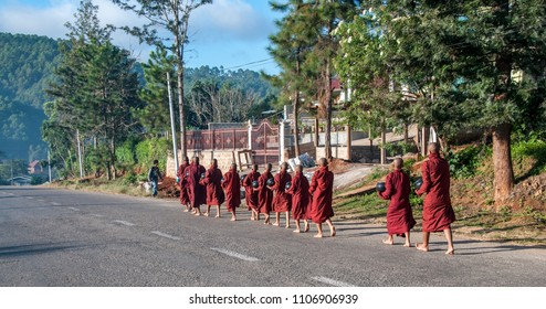 KALAW, MYANMAR - NOV 8, 2012 : Young Buddhist monks in neat row walk the streets of Kalaw for the morning round for the collection of offers, in Kalaw on November 8, 2012.