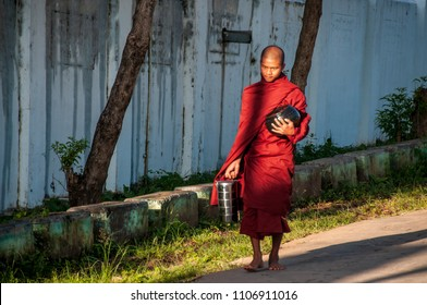 KALAW, MYANMAR - NOV 8, 2012 : A Buddhist monk returns to the Kalaw monastery with the classic food collection pot and a more modern metal pot, in Kalaw on November 8, 2012.