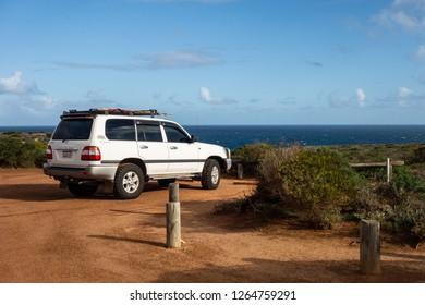KALBARRI, WESTERN AUSTRALIA -  JULY 3, 2018: Legendary 4WD white Toyota Landcruiser car parked in Kalbarri National Park on a beautiful shore of the ocean. Travelling and adventures around Australia.