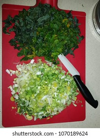 Kale, chard and leeks chopped and piled high on a red cutting board