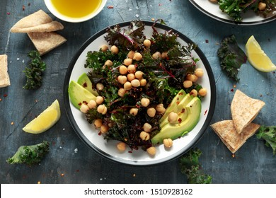 Kale Chickpeas, avocado salad with lemon on plate. healthy food.