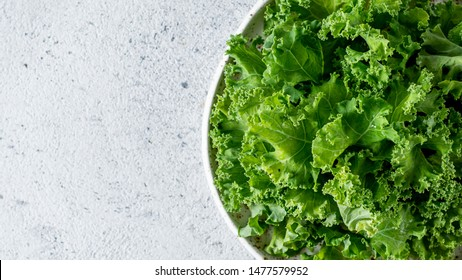 Kale close up. Green vegetable leaves, top view in white craft bowl over gray cement background. Healthy eating, vegetarian food,dieting concept. Top view or flat lay. Copy space. Health kale benefits