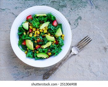 Kale, corn and avocado salad on rustic stone background