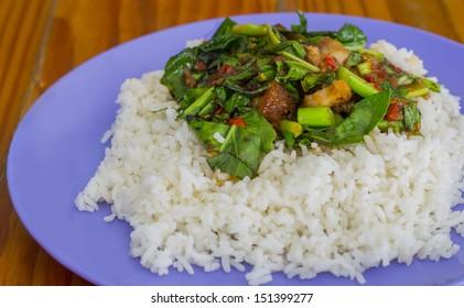 Kale with crispy pork rice on wood table
