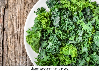 Kale. Green vegetable leaves, top view on white plate, healthy eating, vegetarian food.