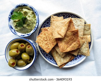Kale hummus with green olives and pita chips on napkin