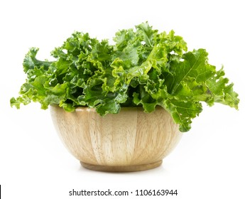 kale leafs in wooden bowl isolated on white background