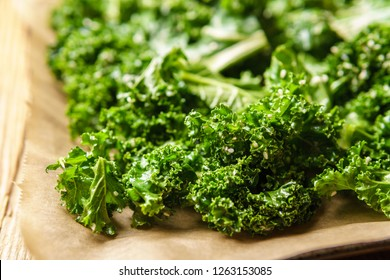 Kale mixed with olive oil, salt, sesame seeds and lemon juice outspread on baking tray, baking paper, textured wooden surface, oven-ready - angled view, close-up, horizontal landscape format