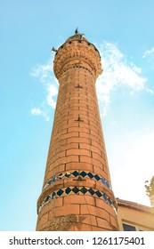 Kale Mosque (Turkish: Dedeki Pasa Camii) and a minaret under white and blue clouds in Yesil Ada of Egirdir. Isparta-Turkey