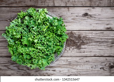 Kale on wooden table with copy space, top view