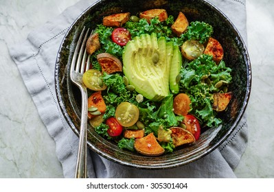 Kale, roasted yams and avocado salad on stone background