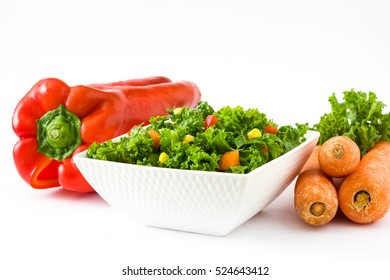 Kale salad in bowl with carrot, pepper and sweet corn isolated on white background