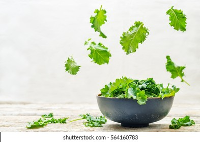 kale salad with flying slices on a wood background. tinting. selective focus