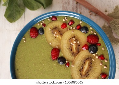 Kale Smoothie Bowl topped with Kiwi slices Pomegranate Buckwheat and Blue berries