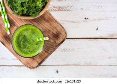Kale smoothie in glass on white wooden background.Top view