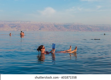 KALIA BEACH, DEAD SEA, ISRAEL - FEBRUARY 27, 2017: Young woman reads a book floating in the waters of the Dead Sea in Israel