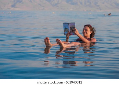 KALIA BEACH, ISRAEL - FEBRUARY 27, 2017:  Young woman reads a book floating in the waters of the Dead Sea in Israel
