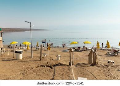 A Kalia beach on Dead sea, Israel,  silhouettes and yellow umbrellas