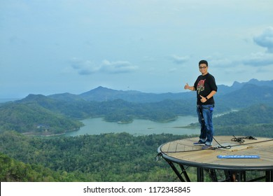Kalibiru,Yogyakarta-August 21st,2017:A man standing on a view point to get a photo with the nature background. Kalibiru is one of the main tourist spot in Yogyakarta,Indonesia.