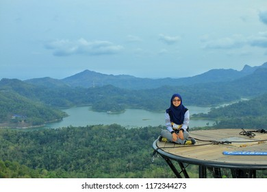 Kalibiru,Yogyakarta-August 21st,2017:A Muslim girl in hijab sitting on a view point to get a photo. Kalibiru is one of the main tourist spot in Yogyakarta,Indonesia.