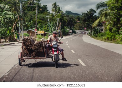 Kalibo, Philippines - January 13, 2016: a man using a motorcycle to move a large amount of wood in a road in Kalibo, Philippines.