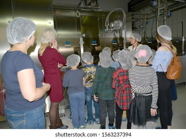 KALININGRAD REGION, RUSSIA - SEPTEMBER 27, 2019: A master tour guide shows students new equipment for chocolate production. Children 's tour to the chocolate factory