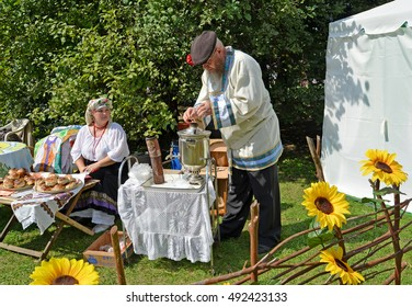 KALININGRAD, RUSSIA - AUGUST 15, 2014: The elderly man kindles a samovar at fair of national creativity