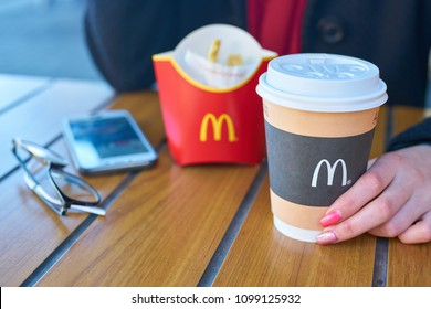 KALININGRAD, RUSSIA - CIRCA APRIL, 2018: woman hold cup of coffee at McDonald's restaurant in Kaliningrad.