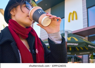 KALININGRAD, RUSSIA - CIRCA APRIL, 2018: young woman drinks a coffee in the background of the McDonald's restaurant.