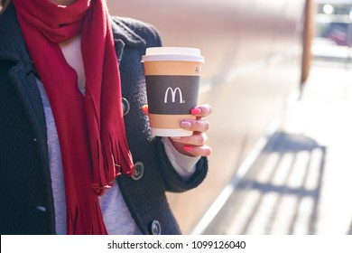 KALININGRAD, RUSSIA - CIRCA APRIL, 2018:  young woman with a cup of coffee from McDonald's in Kaliningrad.