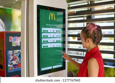 KALININGRAD, RUSSIA - CIRCA SEPTEMBER, 2018: woman use self ordering kiosk in McDonald's restaurant. McDonald's is an American fast food company.