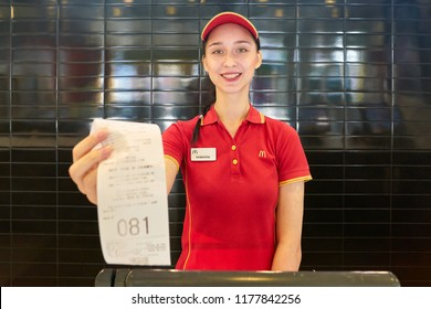 KALININGRAD, RUSSIA - CIRCA SEPTEMBER, 2018: worker hold till receipt in McDonald's restaurant. McDonald's is an American fast food company.