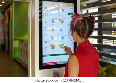 KALININGRAD, RUSSIA - CIRCA SEPTEMBER, 2018: woman use self ordering kiosk in McDonald's restaurant. McDonald's is an American fast food company.