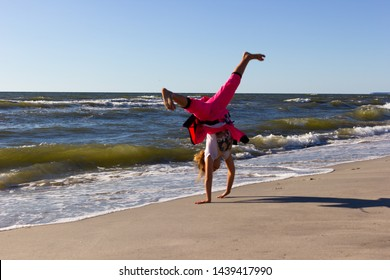Kaliningrad, Russia - June 23, 2019: Little girl doing cartwheel at baltic sea beach in summer day